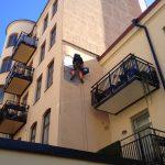 Person som renoverar en husfasad hängandes i klätterlina