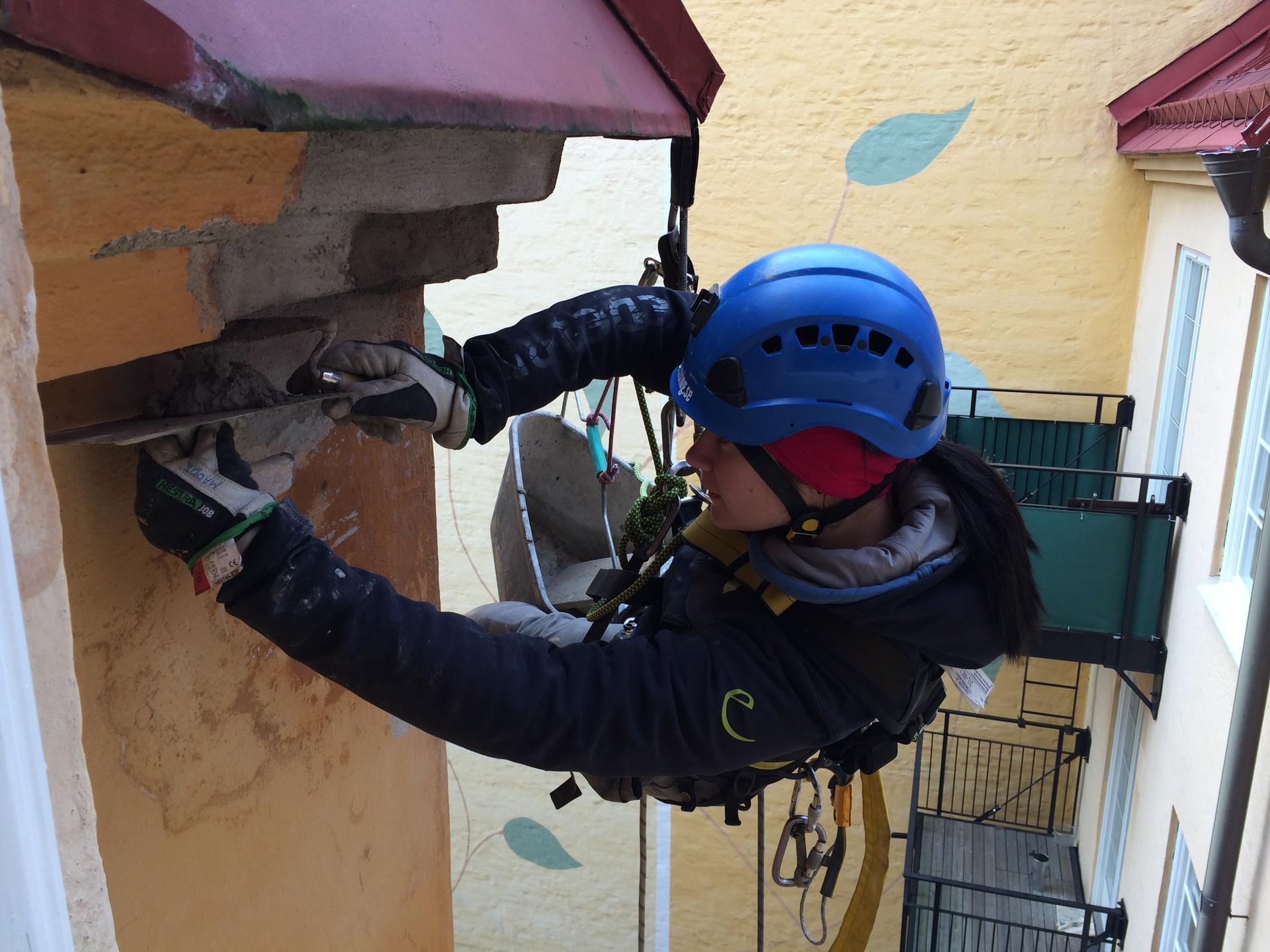 person arbetar och lagar del av fasad