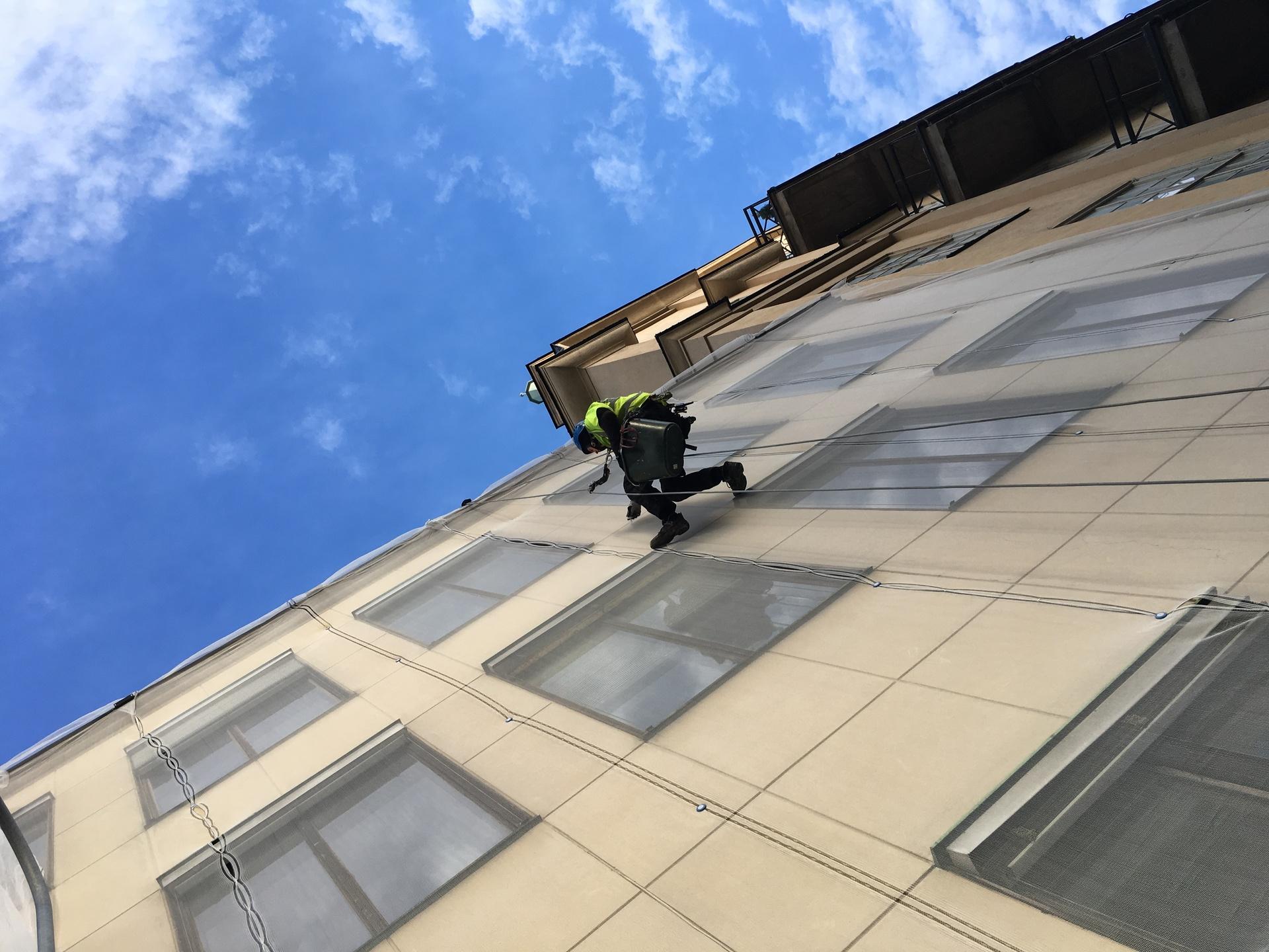 Person som i varselväst klättrar upp för husfasad