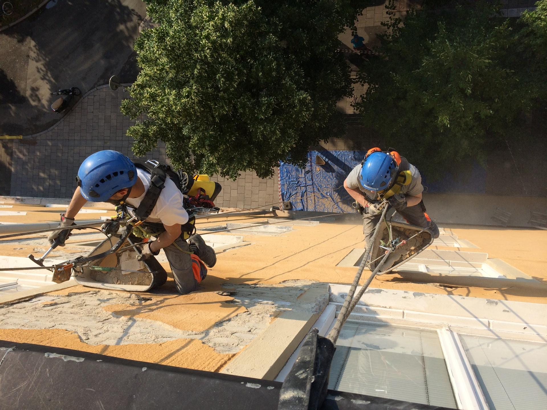 Två personer som renoverar en husfasad