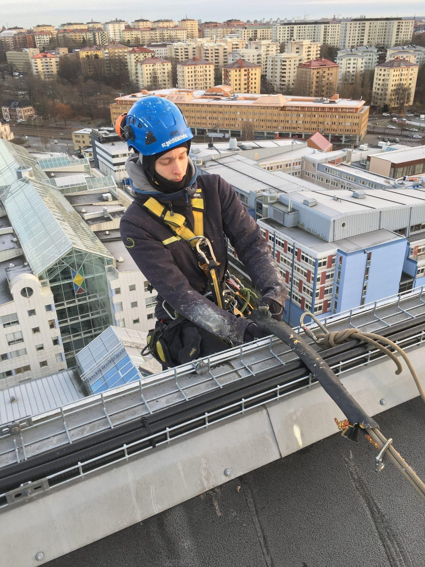 Person i blå skyddshjälm firar ner sig från tak med säkerhetslina