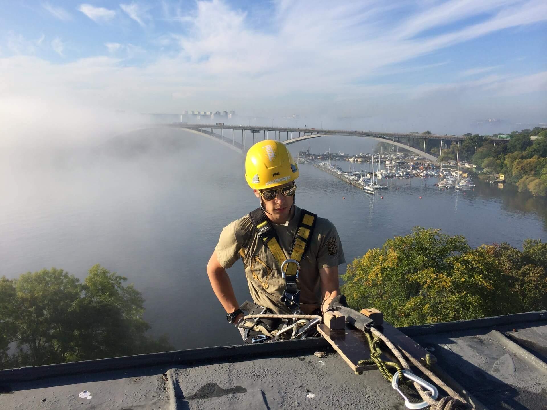 Person i byggarbetarhjälm börjar fira ner sig från tak.